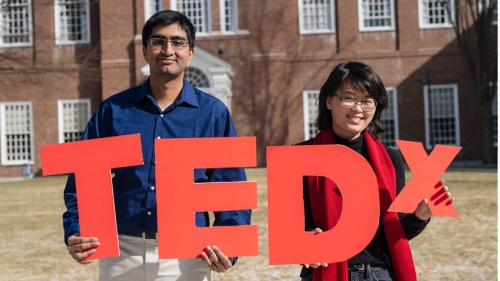 The organizers of TedX Dartmouth hold up cutouts of the letters TEDX