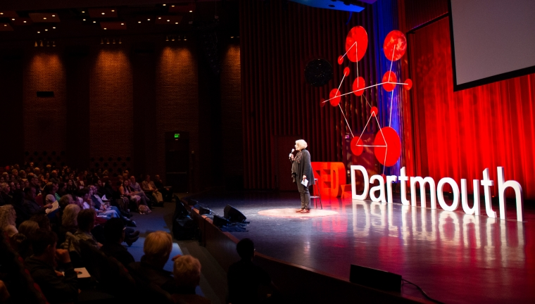Person speaking on stage at TEDx event