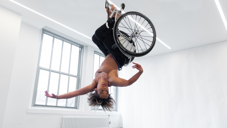Alice Sheppard hovers upside down, suspended from the ceiling in her wheelchair, in a brown leotard and black leggings. She is a light-skinned, multiracial Black woman with short curly hair. Her arms extend as if caught mid-flight. Photo by Mengwen Cao.