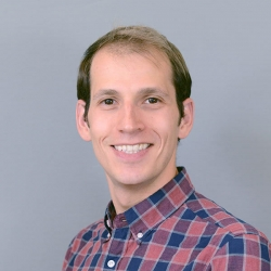 Eugene Korsunskiy, a white man with short brown straight hair, smiles at the camera while his body faces sideways. He is wearing a red and blue plaid shirt and sits against a pale blue gray background. Photo by Katy Lapierre, Thayer Communications